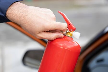 Male hand pulling safety pin of fire extinguisher close up against the background of a car