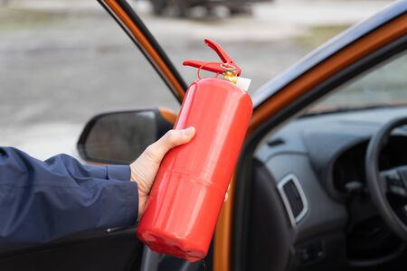 Fire extinguisher in a human hand on the background of the car