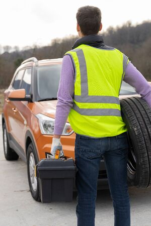 Photo of a driver with tools to repair the car and a spare wheel in his hands, in front of his vehicle. The man is dressed in high-visibility or reflective vest