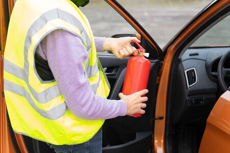 An emergency worker demonstrates how to use a fire extinguisher in the car