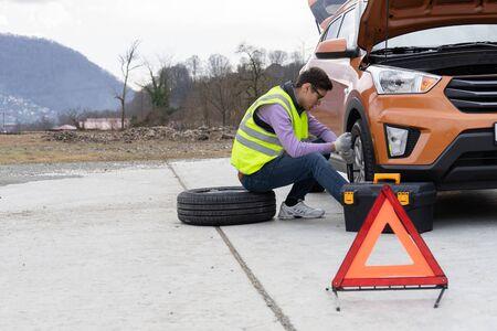 Un mécanicien dans un gilet réfléchissant change une roue sur la route