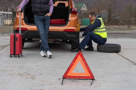 Young man gets a help with spare wheel replacement. Punched wheel on the road while driving. The mechanic is dressed in a reflective vest replacing tires. Emergency stop sign set in front. Reklamní fotografie