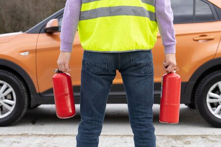 Man with a two fire extinguishers in his hand near the car. Focus on fire extinguisher.