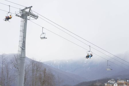 Skiers and snowboarders on a ski lift. Ski resort