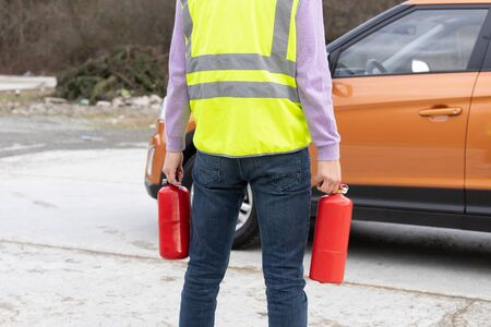 An emergency worker with a two fire extinguishers in his hand, in front of the car. The concept of fire safety