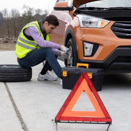 Caucasian young man wearing a high-visibility or hi-vis vest and jeans changing a tire sitting on stepney near car on the roadside. Male changes a damaged wheel on the rural road. Reklamní fotografie