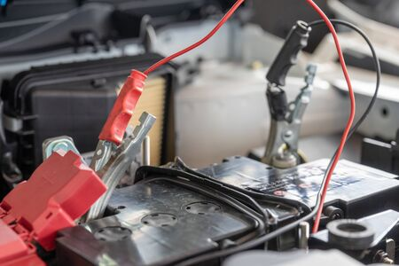 Charging car battery with electricity through jumper cables. Reklamní fotografie
