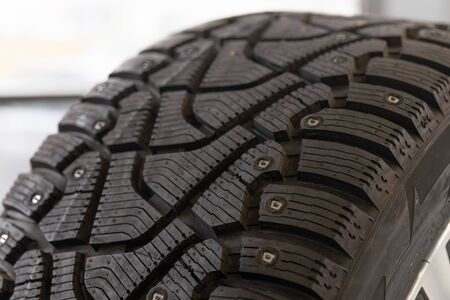 Image of a new winter tire with spikes, close up