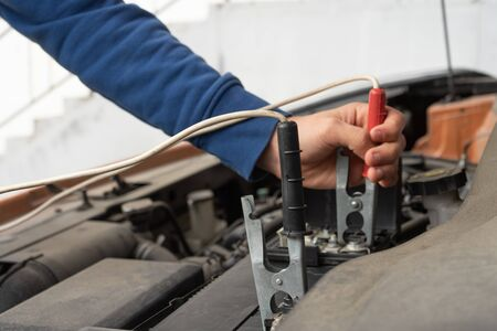 A mechanic using jumper cables to start a car battery.