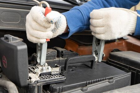 Using jumper cables to charge the car battery.