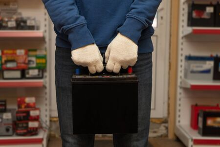 A customer holding a new car battery in an auto parts store