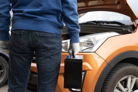 Image of a man holding a new vehicle battery for his car. Rear view Reklamní fotografie