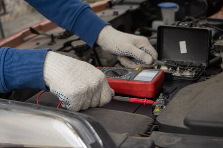 Mechanic using voltmeter checking voltage of car battery in car service centre