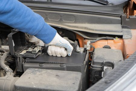 A car mechanic replaces a battery. Maintenance car