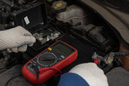 Image of hands with a multimeter voltmeter to check the voltage level in a car battery.