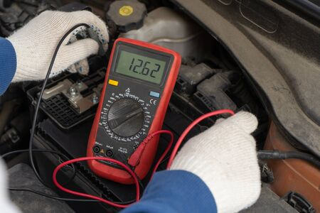 An auto mechanic uses a multimeter voltmeter to check the voltage level in a car battery. Reklamní fotografie