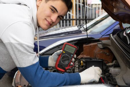 Young man using voltmeter checking voltage of car battery in car service centre