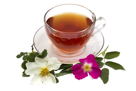 Cup of tea on a saucer with dogrose flowers isolated on a white background