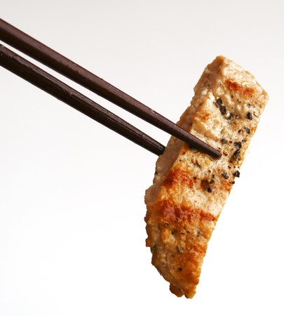 a piece of grilled meat holding by chopsticks photo