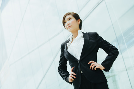 megapolis: Young beautiful businesswoman asian ethnicity standing in front of a glass wall.
