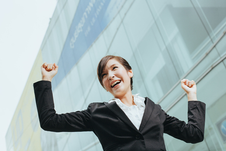 megapolis: Young asian businesswoman rise her arms up as a winner gesture.