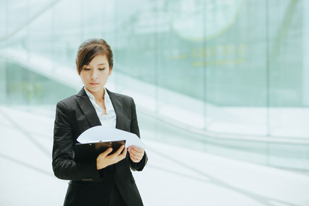 account executive: Young asian businesswoman holding a folder with papers.