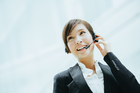 business services: Young asian businesswoman wearing a headphones with microphone.