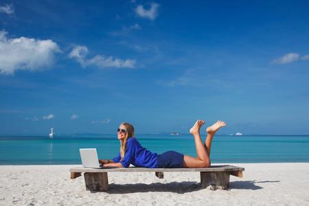 열대 해변에서 노트북을 사용하는 아름 다운 젊은 여자