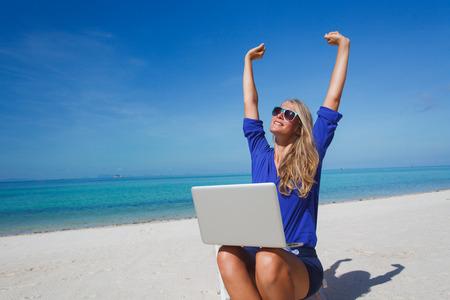 Schöne junge Frau arbeitet mit Laptop auf dem tropischen Strand