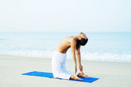 Long Hair Athletic Man with No Shirt doing Yoga on Blue Mat at the Beach