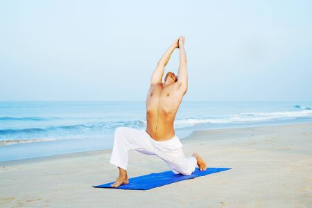 Athletic Man on Mat doing Yoga at the Beach