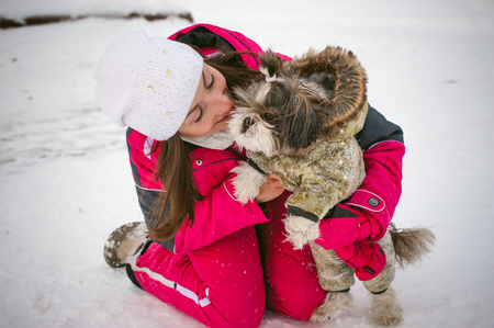 sudadera: Walk in winter outdoors with dog breed Shih Tzu. A woman in bright red warm ski clothing walking in snow with your pet, little shih tzu dressed in overalls. care for animals loves playing with the dog
