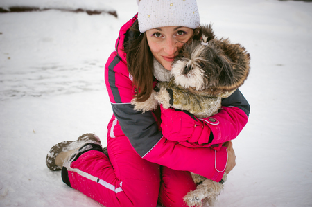ski walking: Walk in winter outdoors with dog breed Shih Tzu. A woman in bright red warm ski clothing walking in snow with your pet, little shih tzu dressed in overalls. care for animals loves playing with the dog