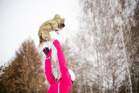dog throws up into the sky. Walk in the winter outdoors with a dog breed Shih Tzu. A woman in a bright red warm ski clothing walking in the snow with your pet, a little shih tzu dressed in overalls. care for animals, and loves playing with the dog