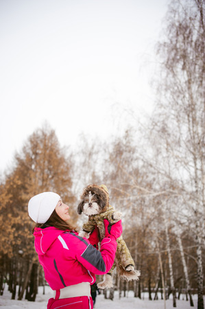 ski walking: dog throws up into the sky. Walk in the winter outdoors with a dog breed Shih Tzu. A woman in a bright red warm ski clothing walking in the snow with your pet, a little shih tzu dressed in overalls. care for animals, and loves playing with the dog