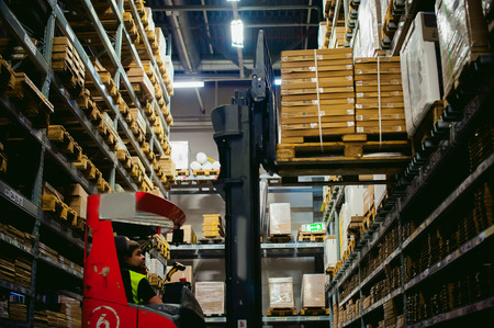 reach truck: young man in working clothes, driver Reachtruck busy working on the logistics warehouse store Stock Photo