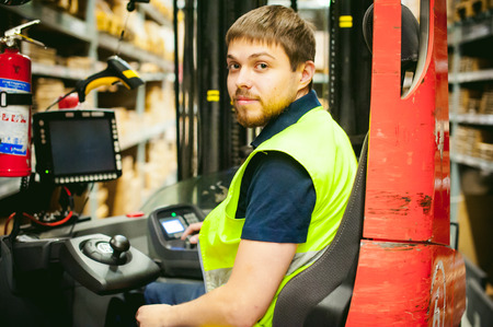 young man in working clothes, driver Reachtruck busy working on the logistics warehouse store Standard-Bild