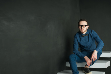 stylishly: studio portrait of a young man on a dark wall background in a blue shirt and jeans. hipster man, dressed stylishly, with a beard and glasses, sitting on white stairs