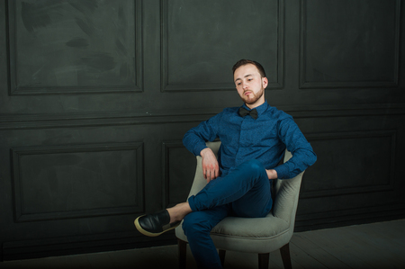 stylishly: studio portrait of a young man on a dark wall background in a blue shirt and jeans. hipster man, dressed stylishly, with a beard, sitting in a light easy chair Stock Photo