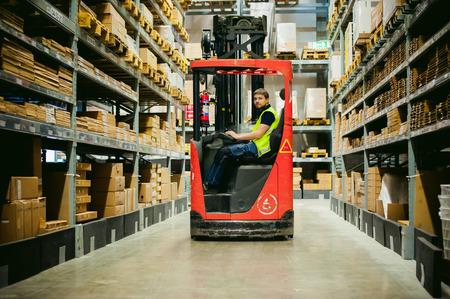 hombre joven en la ropa de trabajo, conductor Retráctiles ocupado trabajando en la tienda de almacén logístico