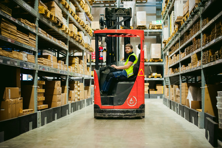 young man in working clothes, driver Reachtruck busy working on the logistics warehouse store Foto de archivo