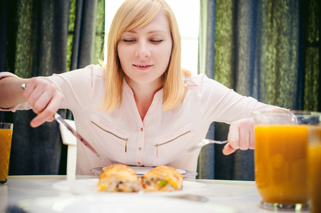 poured: Pretty blonde woman in a pink shirt, eating at home a fork and knife. breakfast sandwich and peach juice. on white table in bright interior of kitchen in plate is sandwich juice poured in glass
