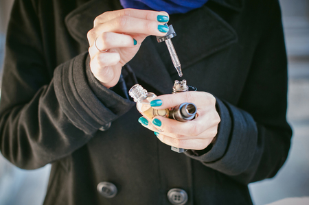 portrait of young beautiful woman with white hair, in a black coat, a skirt and a black hat, smoking an electronic cigarette, runs vape juice electronic cigarette. He holds a mechanical mod with RDA. Standard-Bild