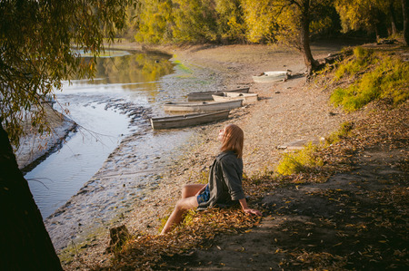 river banks: pretty blonde girl in sneakers, nylon stockings and coat, sits on  banks of river, on yellow leaves, enjoying warmth of autumn sun rays Stock Photo