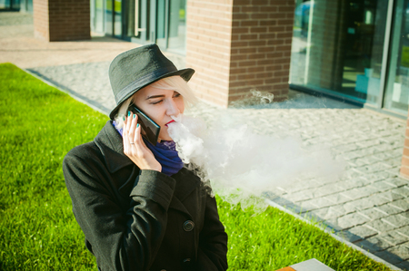 portrait of young beautiful woman with white hair, in a black coat, a skirt and a black hat, talking on cell phone on the street. telephone communication, liaison, pleasant conversation about the business Stock Photo