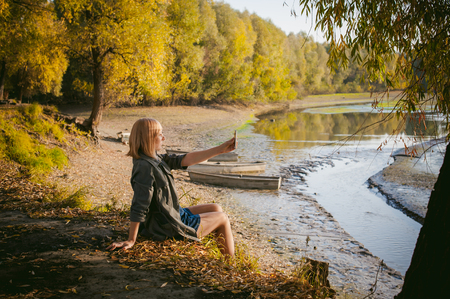 pretty blonde girl in sneakers, nylon stockings and coat. photographed on a smartphone selfie, sits on banks, on yellow leaves, enjoying warmth of autumn sun