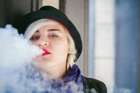 portrait of young beautiful woman with white hair, in a black coat, a skirt and a black hat, smoking an electronic cigarette, blowing the smoke vapor Stock Photo