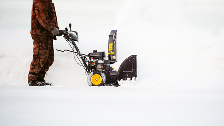 man operating snow blower to remove snow on driveway Stock Photo