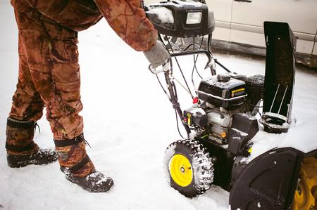 man starts the engine snow blower Stock Photo