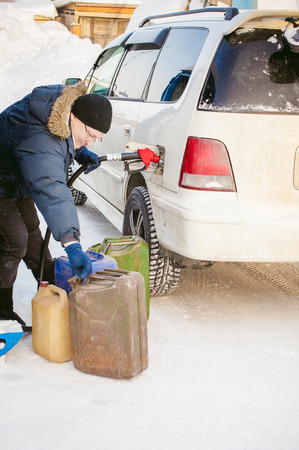 adult man fills a car with petrol at a fuel station in the winter. refueling nozzle man holding in his hand, pouring the liquid in the canister and fuel tank
